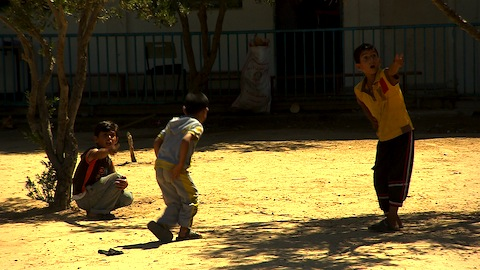 Children at a UN-run shelter point as Hamas rockets are fired overhead